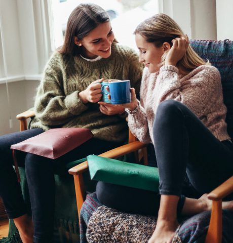 Canva - Two Women Smiling and Talking While Sitting on Chair and Holding a Mug